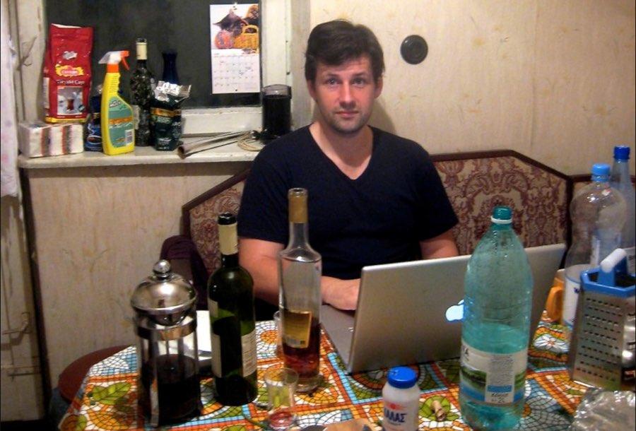 Maciej devant son ordinateur dans une cuisine en bazar