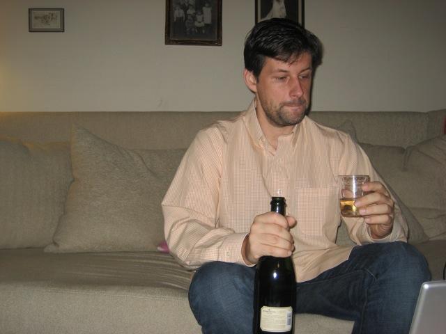 Maciej assis sur un canapé, avec une bouteille de champagne et un verre à la main, devant son ordinateur